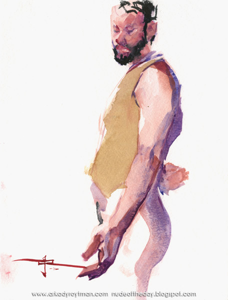 Devin In A Tan Vest, Standing In Profile, Looking Down At His Outstretched Left Hand